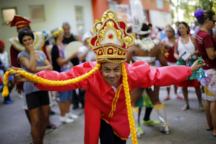 """A patient from the Nise de Silveira mental health institute dances in costume during the institute's carnival parade, coined in Portuguese: """"Loucura Suburbana,"""" or Suburban Madness, in the streets of Rio de Janeiro, Brazil, Thursday, Feb. 12, 2015. Patients, their relatives and workers from the institute held their parade one day before the official start of Carnival. (AP Photo/Silvia Izquierdo)"""