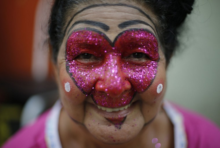 """A patient from the Nise de Silveira mental health institute wearing face paint smiles to the camera during the institute's carnival parade, coined in Portuguese: """"Loucura Suburbana,"""" or Suburban Madness, in Rio de Janeiro, Brazil, Thursday, Feb. 12, 2015. Patients, relatives and workers of the institute held their parade one day before the official start of Carnival. (AP Photo/Silvia Izquierdo)"""