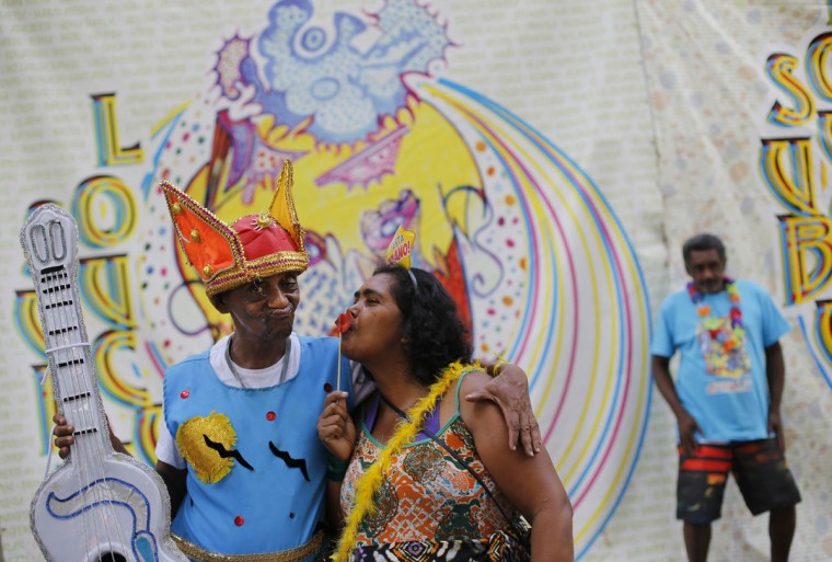 """Patients from the Nise de Silveira mental health institute stand in costume before the institute's carnival parade, coined in Portuguese: """"Loucura Suburbana,"""" or Suburban Madness, in Rio de Janeiro, Brazil, Thursday, Feb. 12, 2015. Patients, relatives and workers of the institute held their parade one day before the official start of Carnival. (AP Photo/Silvia Izquierdo)"""