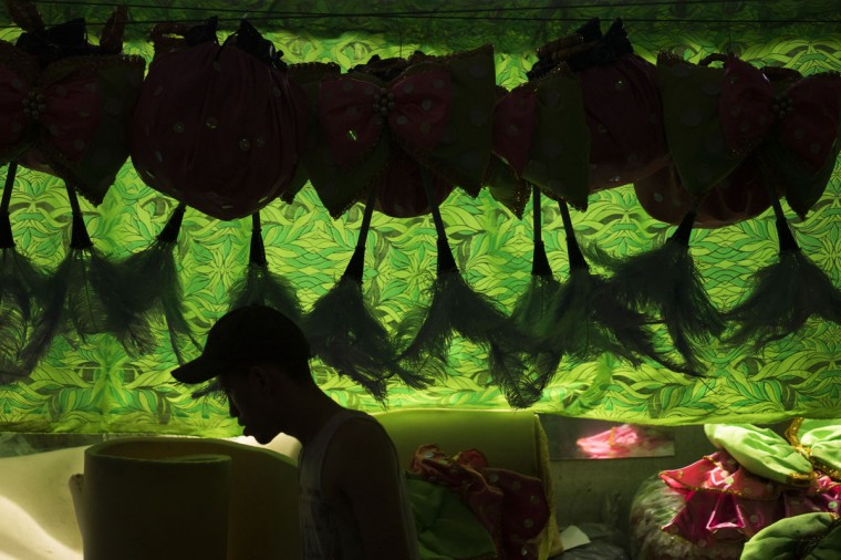 A worker walk past carnival costumes at the Mangueira Samba school in Rio de Janeiro, Brazil, Tuesday, Feb. 3, 2015. Brazil has begun preparing for its pre-Lenten world famous festival that starts on Feb. 13. (AP Photo/Felipe Dana)