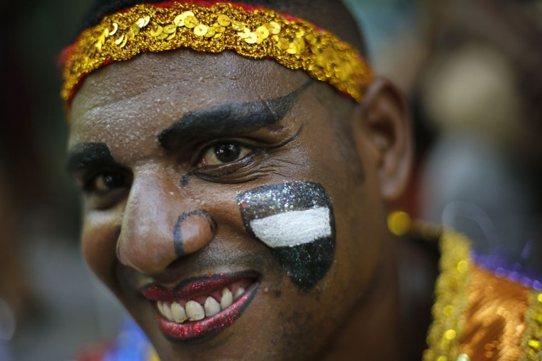"""A patient in costume from the Nise de Silveira mental health institute waits for the start of the institute's carnival parade, coined in Portuguese: """"Loucura Suburbana,"""" or Suburban Madness, in Rio de Janeiro, Brazil, Thursday, Feb. 12, 2015. Patients, their relatives and workers from the institute held their parade one day before the official start of Carnival. (AP Photo/Silvia Izquierdo)"""
