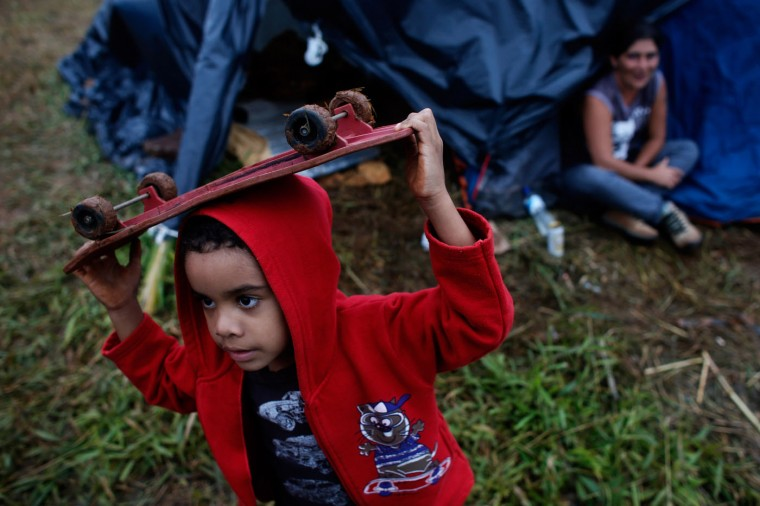 In this Feb. 8, 2015 photo, Gustavo, 6, carries his skateboard on his head as he walks in front of makeshift tents at a Homeless Workers Movement squatters camp in the Ceilandia neighborhood of Brasilia, Brazil. Young Gustavo and his family are part of a group of almost 3,000 homeless people that invade lands and buildings in cities across Brazil, which have in recent days pitched their paltry shelters on six large tracts of land in and around Brasilia. (AP Photo/Eraldo Peres)
