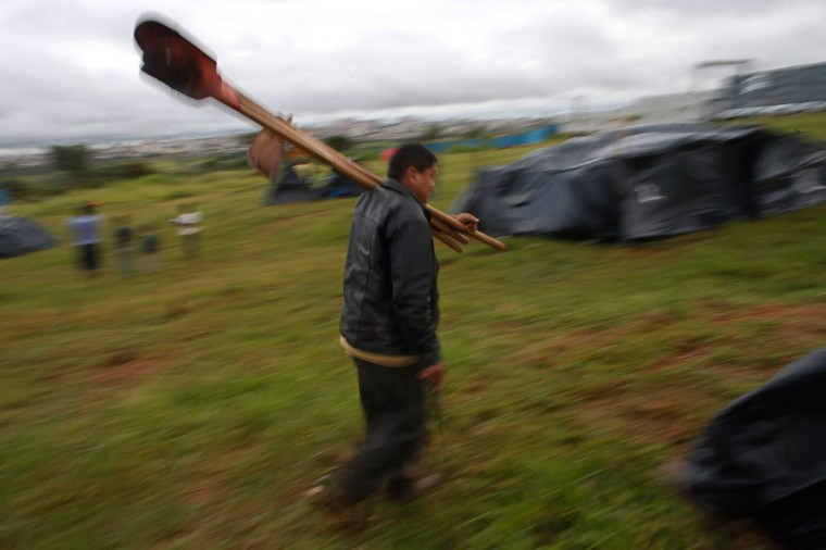 In this Feb. 8, 2015 photo, a man carries farm implements at a Homeless Workers Movement squatters camp the Ceilandia neighborhood in Brasilia, Brazil. The farm implements are used to dig holes for posts in order to set up new makeshift tents in the camp. (AP Photo/Eraldo Peres)