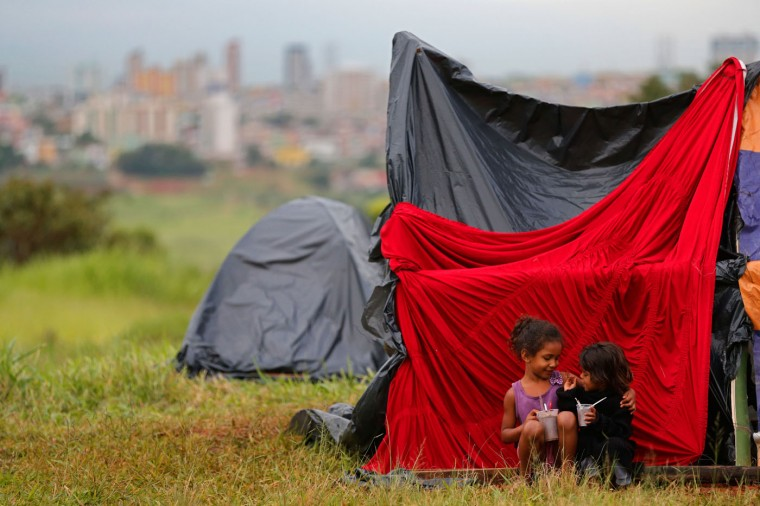 In this Feb. 9, 2015 photo, Estafani, 5, right, and Amanda, 7, play outside their makeshift tent at a Homeless Workers Movement squatters camp in the Ceilandia neighborhood of Brasilia, Brazil. Leaders of the homeless group and government officials have come to an agreement that as authorities promised to set aside land for low-income house projects for those in the camps, in return for them leaving the land they had occupied. (AP Photo/Eraldo Peres)