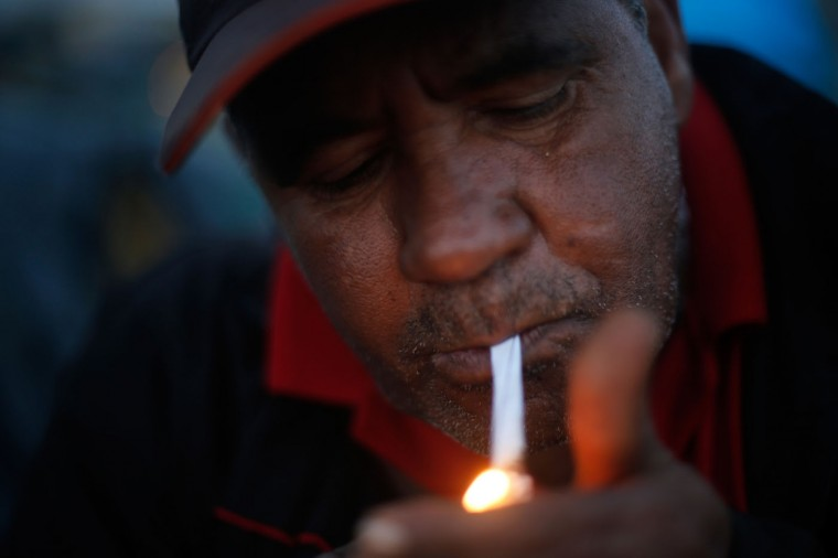 In this Feb. 8, 2015 photo, Humberto Ribeiro, 54, lights a cigarette at a Homeless Workers Movement squatters camp in the Ceilandia neighborhood of Brasilia, Brazil. Ribeiro who says that he has lived in Brasilia for the last 40 years stands watch at night in the camp to prevent others who are not members of the Homeless Workers Movement to enter the area. (AP Photo/Eraldo Peres)