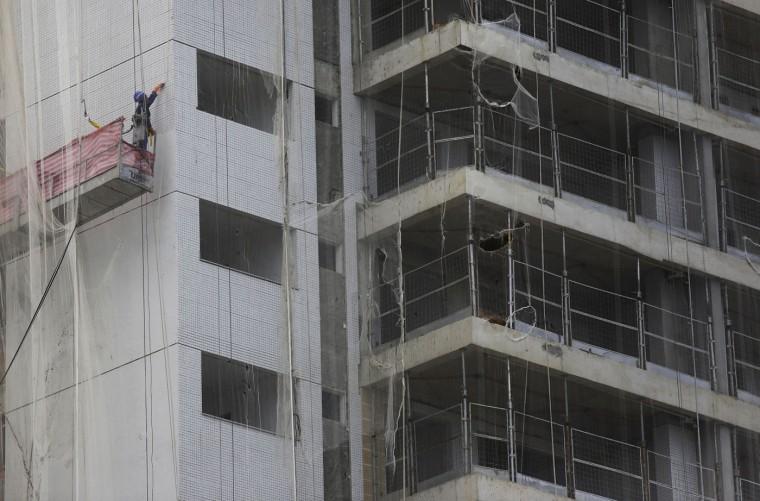 A man works at the 2016 Olympic Games's Athletes Village under construction in Rio de Janeiro, Brazil, Thursday, Feb. 19, 2015. (AP Photo/Leo Correa)