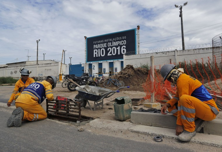 """Men work in front of a the Olympic Park's entrance, that reads in Portuguese: """"Future facilities of the Olympic Park Rio 2016,"""" in Rio de Janeiro, Brazil Thursday, Feb. 19, 2015. (AP Photo/Leo Correa)"""