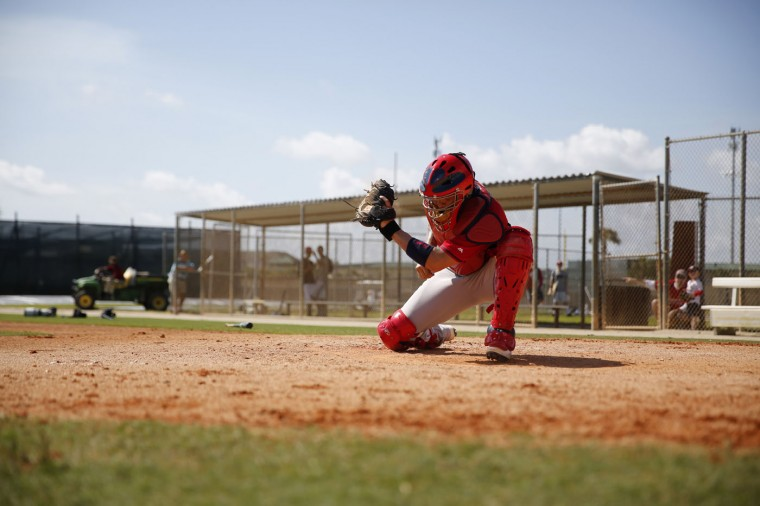 St. Louis Cardinals catcher Yadier Molina swipes at the plate on a defense drill during spring training baseball practice Sunday, Feb. 22, 2015, in Jupiter, Fla. (AP Photo/Jeff Roberson)