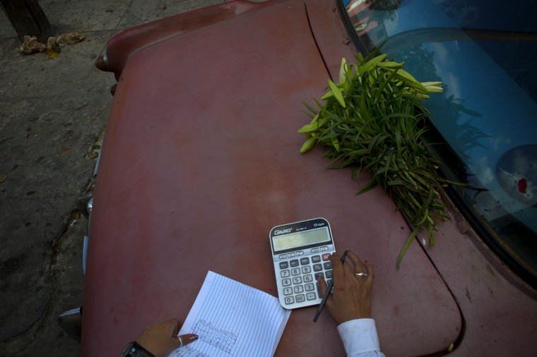 In this Thursday, Jan. 29, 2015 photo, self-employed flower vendor Yaima Gonzalez Matos, 33, tallies her sales, in Havana, Cuba. The smallest mishap can push her balance sheet into the red for weeks. Recently someone reached into her rented car and stole her cellphone while she was talking to a client. Some days, the 1957 Buick she rents to transport the flowers, breaks down, leaving her stranded on the roadside.(AP Photo/Ramon Espinosa)