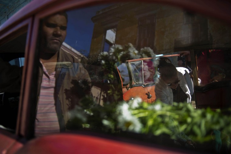 In this Thursday, Jan. 29, 2015 photo, self-employed flower vendor Yaima Gonzalez, 33, right, sells flowers from a 1957 parked Buick she has rented for the day, in Havana, Cuba. Every Monday and Thursday, Gonzalez leaves her home in San Antonio de los Banos, a town outside Havana, to visit a dozen farmers who sell her the blooms and with the help of Lazaro the taxi driver, she loads into the Buick and begins her deliveries to customers in the capital. (AP Photo/Ramon Espinosa)
