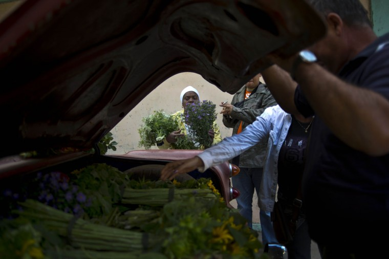 In this Thursday, Jan. 29, 2015 photo, customers gather around self-employed flower vendor Yaima Gonzalez Matos, 33, shopping for bouquets of flowers, in Havana, Cuba, from Gonzalez's makeshift flower stand; a 1957 Buick she rents for the day to transport the flowers from nearby farms into the capital. On a good day, she earns about $28 after expenses, a little more than the average monthly salary in Cuba. (AP Photo/Ramon Espinosa)