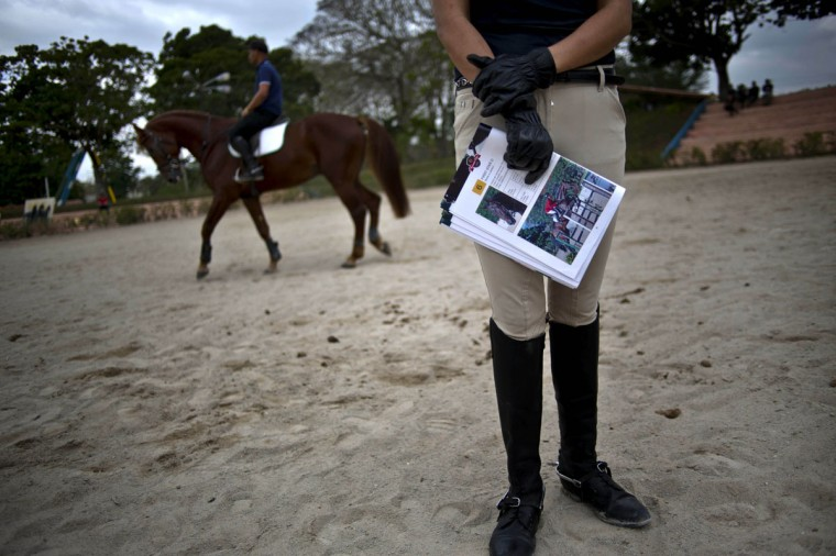 Cecilia Pedraza, a Mexico City collector who bought several of Dutch Warmbloods horses, holds a magazine that lists horses for auction at the National Equestrian Club in Lenin Park on the outskirts of Havana, Cuba. ìThe great advantage is that they are already in the Americas,î said Pedraza. ìIn addition, they have been trained very well. They are advanced for their age, very well-behaved, perform concentrated jumps and have excellent blood lines.î (AP Photo/Ramon Espinosa)
