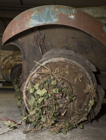 Weeds are still attached to a Delage D6-11 S coach displayed during a preview for an auction of vintage cars Retromobile show in Paris, Tuesday, Feb. 3, 2015, after a treasure trove of classic cars was discovered after spending 50-years languishing in storage on a farm. 60 rusting motors, which include a vintage Ferrari California Spider, a Bugatti and a very rare Maserati, were found gathering dust and hidden under piles of newspapers in garages and outbuildings at a property in France. The cars were collected from the 1950s to the 1970s by entrepreneur Roger Baillon, who dreamt of restoring them to their former glory and displaying them in a museum, but, his plans were dashed as his business struggled, forcing the sale of about 50 vehicles, to be auctioned off on Feb. 6. (AP Photo/Jacques Brinon)