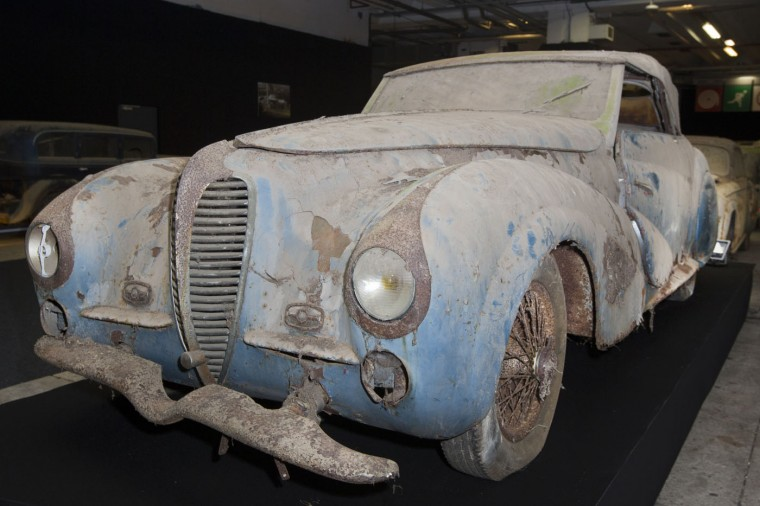 A Delahaye 135-M cabriolet Faget-Varnet is displayed during a preview for an auction of vintage cars Retromobile show in Paris, Tuesday, Feb. 3, 2015, after a treasure trove of classic cars was discovered after spending 50-years languishing in storage on a farm. 60 rusting motors, which include a vintage Ferrari California Spider, a Bugatti and a very rare Maserati, were found gathering dust and hidden under piles of newspapers in garages and outbuildings at a property in France. The cars were collected from the 1950s to the 1970s by entrepreneur Roger Baillon, who dreamt of restoring them to their former glory and displaying them in a museum, but, his plans were dashed as his business struggled, forcing the sale of about 50 vehicles, to be auctioned off on Feb. 6. (AP Photo/Jacques Brinon)