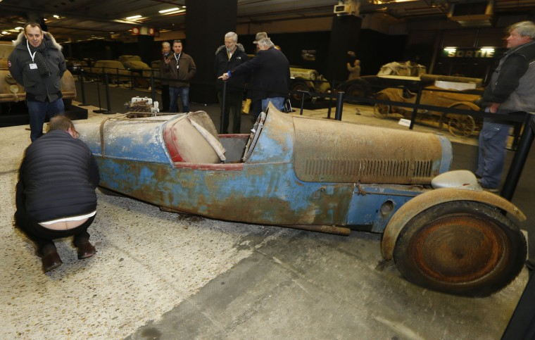 A car enthusiastic checks out a Sandford Type S Cyclecar during a preview for an auction of vintage cars Retromobile show in Paris, Tuesday, Feb. 3, 2015, after a treasure trove of classic cars was discovered after spending 50-years languishing in storage on a farm. 60 rusting motors, which include a vintage Ferrari California Spider, a Bugatti and a very rare Maserati, were found gathering dust and hidden under piles of newspapers in garages and outbuildings at a property in France. The cars were collected from the 1950s to the 1970s by entrepreneur Roger Baillon, who dreamt of restoring them to their former glory and displaying them in a museum, but, his plans were dashed as his business struggled, forcing the sale of about 50 vehicles, to be auctioned off on Feb. 6. (AP Photo/Jacques Brinon)