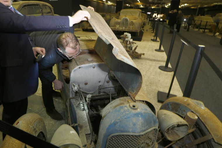 A car enthusiast checks the engine of a Sandford Type S Cyclecar during a preview for an auction of vintage cars Retromobile show in Paris, Tuesday, Feb. 3, 2015, after a treasure trove of classic cars was discovered after spending 50-years languishing in storage on a farm. 60 rusting motors, which include a vintage Ferrari California Spider, a Bugatti and a very rare Maserati, were found gathering dust and hidden under piles of newspapers in garages and outbuildings at a property in France. The cars were collected from the 1950s to the 1970s by entrepreneur Roger Baillon, who dreamt of restoring them to their former glory and displaying them in a museum, but, his plans were dashed as his business struggled, forcing the sale of about 50 vehicles, to be auctioned off on Feb. 6. (AP Photo/Jacques Brinon)
