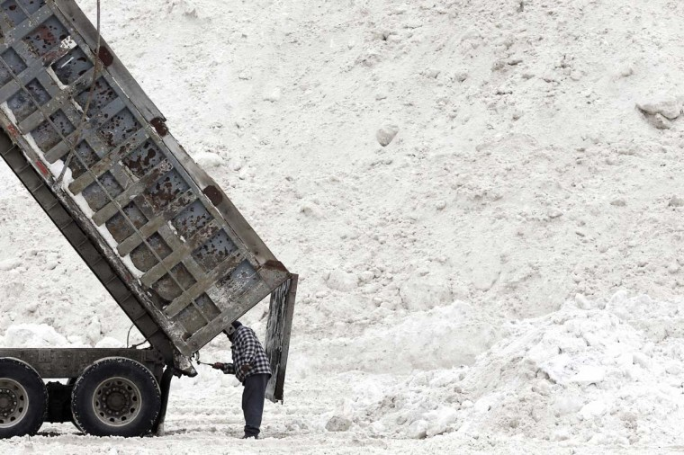 """Evon Daley, of Hartford, Conn., clears his truck after unloading snow at a """"snow farm"""" in Boston. Crews from around the region have worked urgently to remove the massive amounts of snow that has clogged streets and triggered numerous roof collapses ahead of yet another winter storm due to arrive on Saturday. AP Photo/Michael Dwyer"""