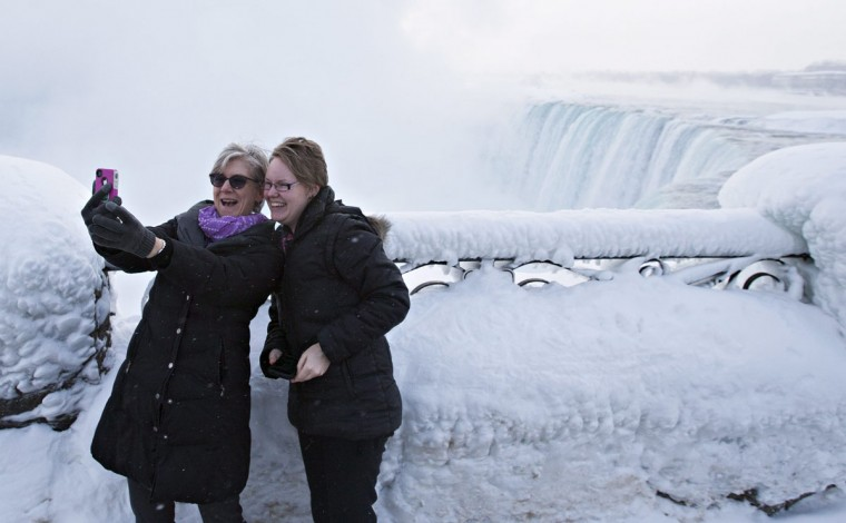 Visitors Rosalie Vissers, left, and Rachel Houter take a photo near masses of ice formed around the Canadian 'Horseshoe' Falls in Niagara Falls, Ontario, Canada, Thursday, Feb. 19, 2015. (AP Photo/The Canadian Press,Aaron Lynett)
