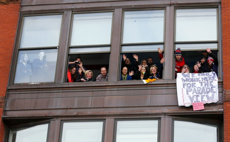 Workers cheer from a window during a parade in Boston, Wednesday, Feb. 4, 2015, to honor the New England Patriots' victory over the Seattle Seahawks in Super Bowl XLIX in Glendale, Ariz. (AP Photo/Winslow Townson)