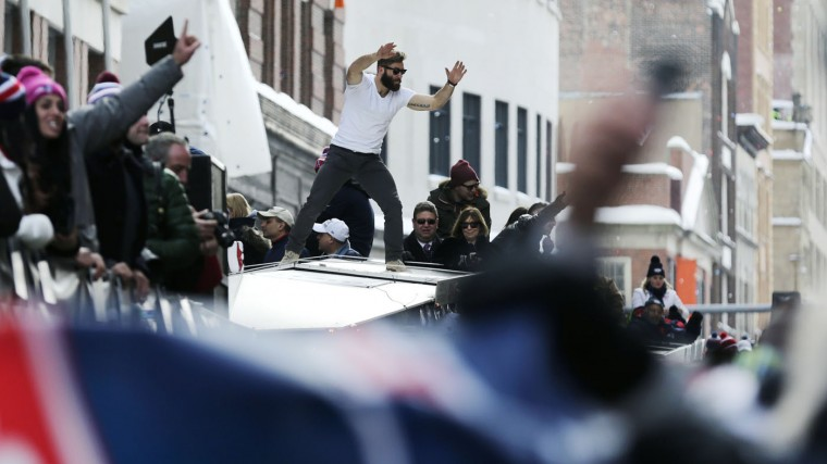 New England Patriots wide receiver Julian Edelman cheers with fans as he rides on the roof of a duck boat during a parade in Boston, Wednesday, Feb. 4, 2015, to honor the NFL football teams victory over the Seattle Seahawks in Super Bowl XLIX in Glendale, Ariz. (AP Photo/Charles Krupa)