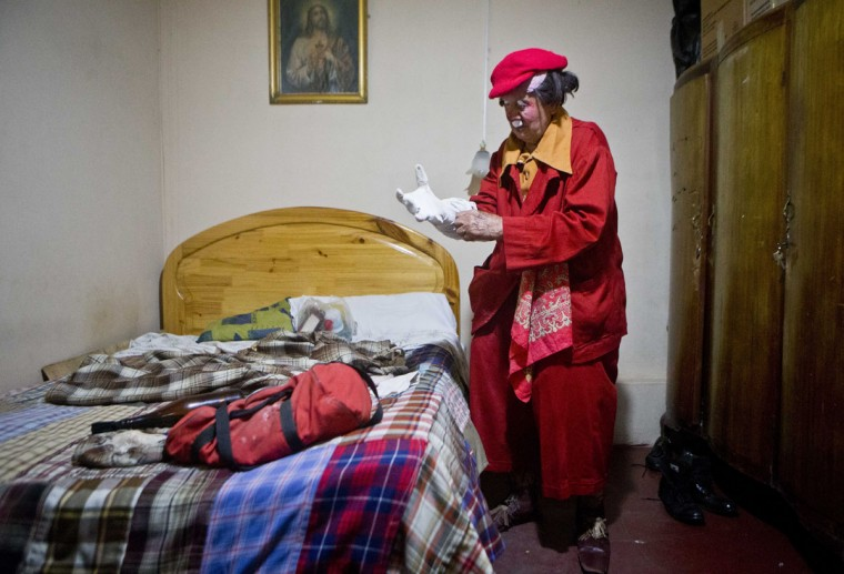 "Veteran clown Ricardo Farfan, popularly known as ""Pitito,"" puts on his costume as he prepares to perform at his 91st birthday party inside his home in Lima, Peru. Farfan started working as a clown and circus performer at the age of three with his father's Farfan Brothers Circus in 1927. (AP Photo/Esteban Felix)"
