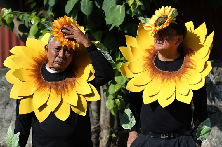 "Filipino residents arrange their flower costumes during the start of the annual ""Caracol"" festival in suburban Makati, south of Manila, Philippines on Sunday, Feb. 22, 2015. The event aims to promote public awareness on environmental issues and cultural heritage. (AP Photo/Aaron Favila)"