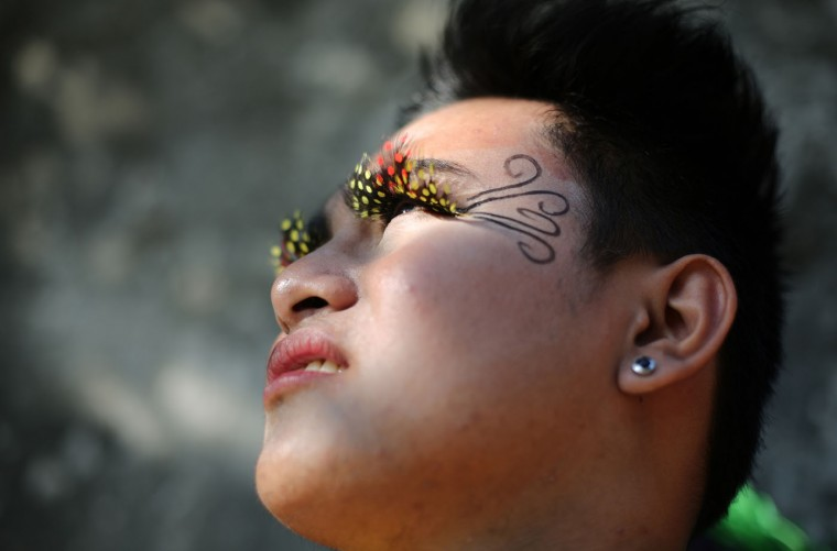 "Filipino student John Bryan Cerbo wears a flower costume as he joins the annual ""Caracol"" festival in suburban Makati, south of Manila, Philippines Sunday, Feb. 22, 2015. The event aims to promote public awareness on environmental issues and cultural heritage. (AP Photo/Aaron Favila)"