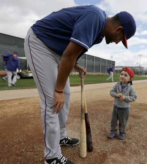 Texas Rangers' Nomar Mazara talks to two-year-old Colin McMahon during spring training baseball practice Monday, Feb. 23, 2015, in Surprise, Ariz. (AP Photo/Charlie Riedel)