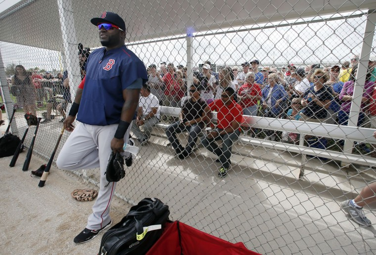Boston Red Sox's David Ortiz takes a breather against the dugout fence as fans watch infielders take fielding drills at baseball spring training in Fort Myers Fla., Wednesday Feb. 25, 2015. (AP Photo/Tony Gutierrez)