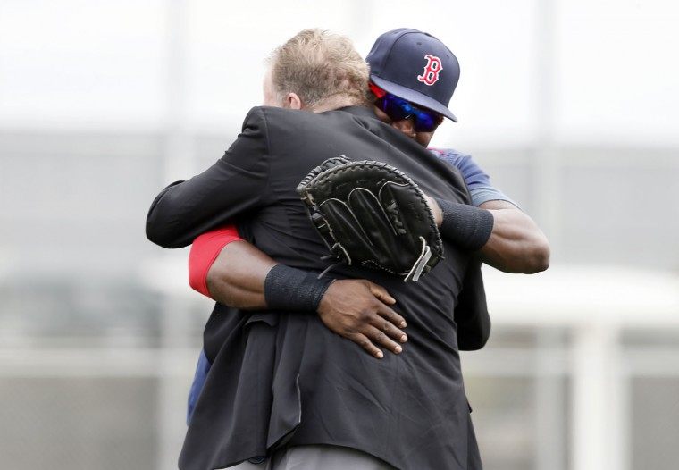 Boston Red Sox's David Ortiz hugs broadcast baseball analyst and former Red Sox pitcher Curt Schilling, front, during a workout at baseball spring training in Fort Myers Fla., Wednesday Feb. 25, 2015. (AP Photo/Tony Gutierrez)