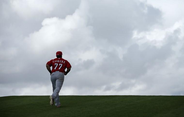 Cincinnati Reds' Ramon Cabrera runs up a hill during a spring training baseball workout Monday, Feb. 23, 2015, in Goodyear, Ariz. (AP Photo/John Locher)