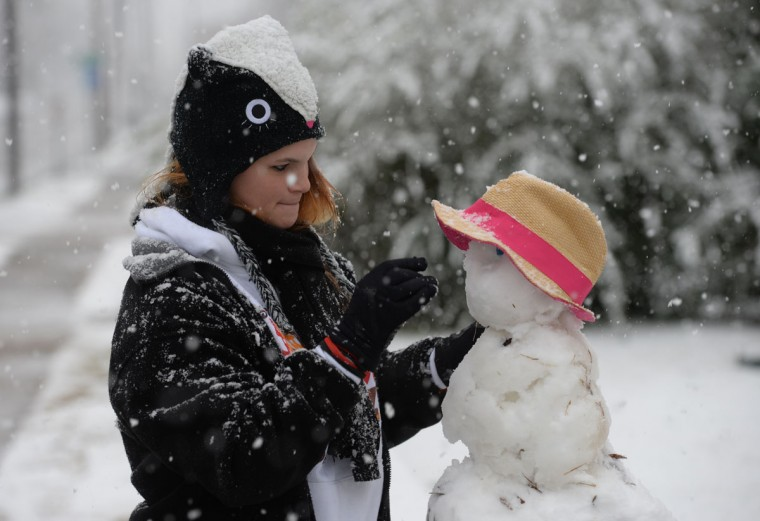 Dallas Burnett puts the finishing touches on a snowman in front of her home as snow falls Wednesday, Feb. 25, 2015, in Shreveport, La. (AP Photo/The Shreveport Times, Douglas Collier)