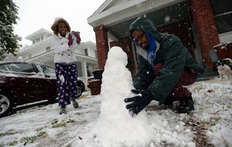 Demarlon Morris, right, and his sister Martina, take advantage of the fresh snow in their yard to build a snowman, Wednesday, Feb. 25, 2015, in Shreveport, La. (AP Photo/The Shreveport Times, Douglas Collier)