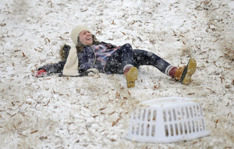A student laughs after sliding down a hill on the University of Mississippi campus, Wednesday, Feb. 25, 2015, in Oxford, Miss. (AP Photo/The Daily Mississippian, Thomas Graning)