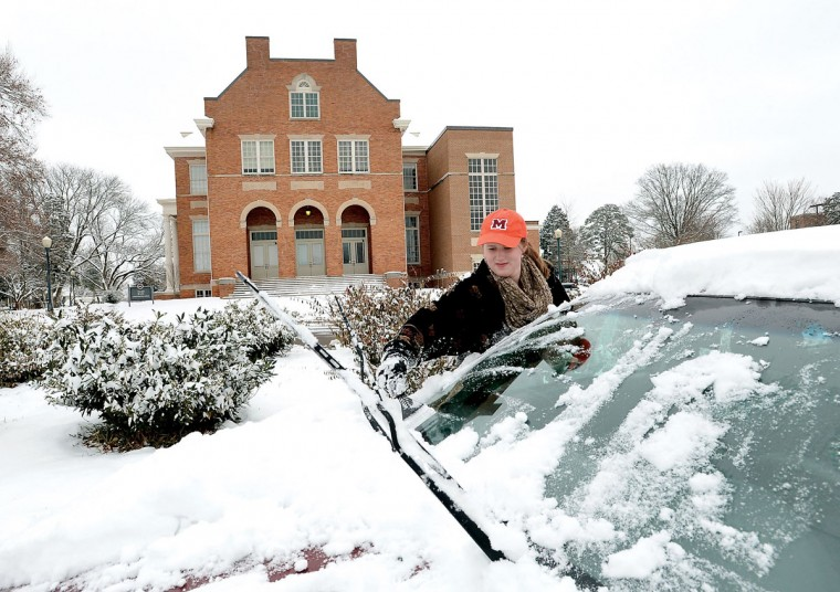 Maryville College student Jenny LaFreniere cleans snow off her car after weather caused a cancellation of classes, Tuesday, Feb. 24, 2015, in Maryville, Tenn. A wide swath of the country is experiencing record-breaking temperatures while other areas are expecting more winter precipitation Tuesday. (AP Photo/The Daily Times, Joy Kimbrough)