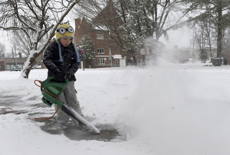 Five-year-old Niko Christian works to remove snow from the sidewalk in front of his house Tuesday, Feb. 24, 2015 in Knoxville, Tenn. The Knoxville area is expected to see between 2 to 40 inches of snowfall by the afternoon.(AP Photo/Knoxville News Sentinel, Amy Smotherman Burgess)