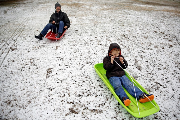 Eric Thomas, left, laughs as he and Ezra Thomas, 5, attempt to sled in what little snow accumulated on Flag Pole Hill, Wednesday, Feb. 25, 2015, in Dallas (AP Photo/The Dallas Morning News, G.J. McCarthy)