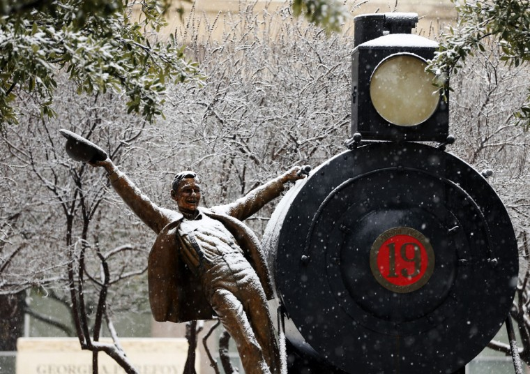 A statue is covered with snow outside the George A. Purefoy Municipal Center as snow falls in Frisco, Texas, Wednesday, Feb. 25, 2015. (AP Photo/The Dallas Morning News, Vernon Bryant)