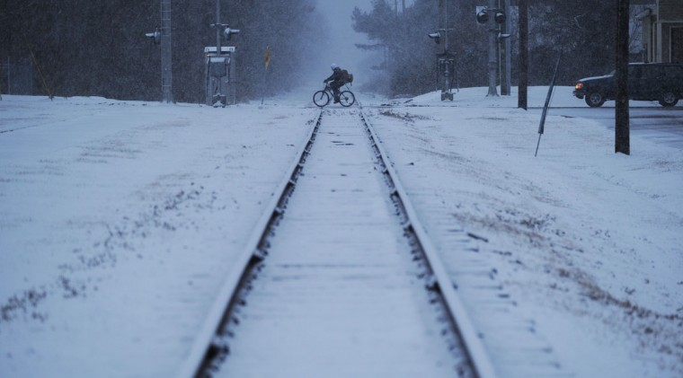 A man rides his bicycle across the railroad tracks in Exmore, Va. as snow falls, Tuesday, Feb. 24, 2015. (AP Photo/Eastern Shore News, Jay Diem)