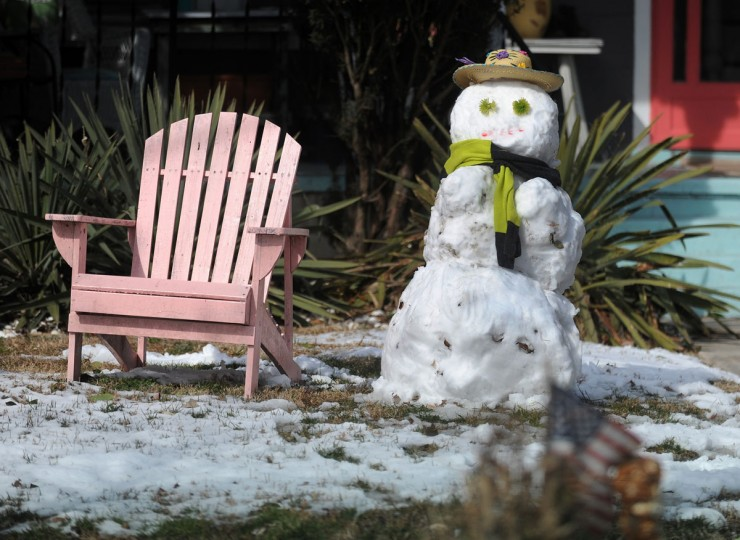 A snowman stands next to a wooden deck chair on Randolph Avenue in Cape Charles, Va. on Wednesday, Feb. 25, 2015. (AP Photo/Eastern Shore News, Jay Diem)