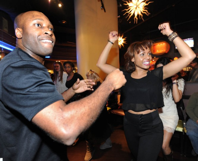"Brandon ""Bachata"" Ross, left, and Nancy Alers, alias Nancy ""Salsa,"" center, both with Sentimiento Latin Dance Company which runs the salsa class in partnership with Rueda de Casino Baltimore, demonstrate salsa moves. (Algerina Perna/Baltimore Sun)"