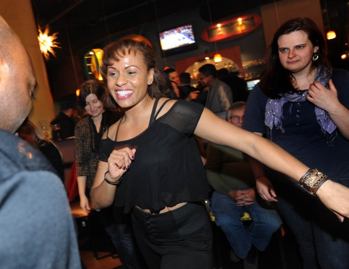 """Nancy Alers, alias Nancy """"Salsa,"""" center, with Sentimiento Latin Dance Company which runs the salsa class in partnership with Rueda de Casino Baltimore, gives a demonstration with Brandon """"Bachata"""" Ross, also from Sentimiento, left. (Algerina Perna/Baltimore Sun)"""