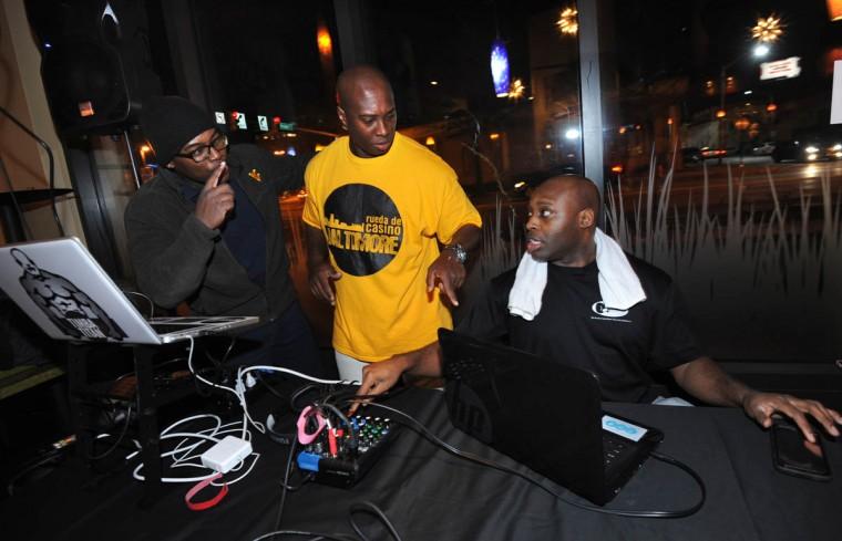 "Cedric Teamer with Rueda de Casino Baltimore, center, and Brandon ""Bachata"" Ross, right, with Sentimiento Latin Dance Company, both double as DJs and salsa instructors.(Algerina Perna/Baltimore Sun)"