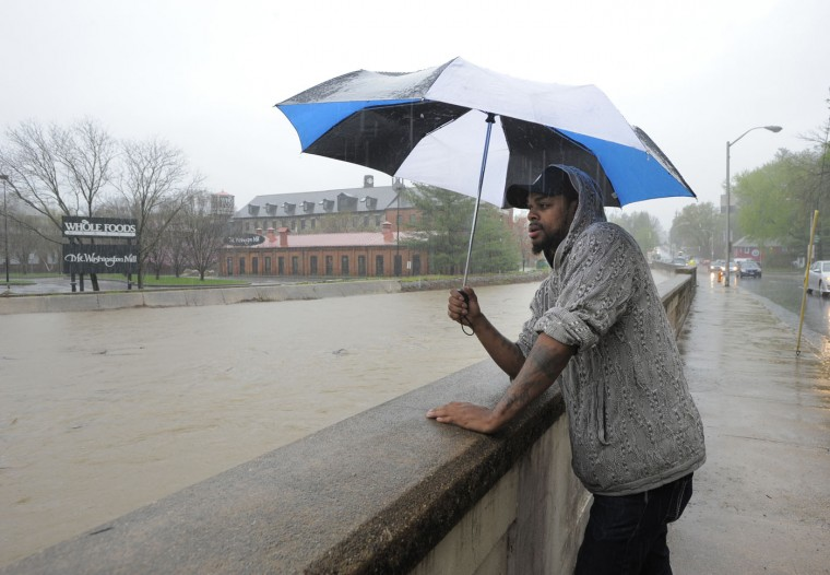 Terrell Jarrell of Baltimore looks out at the rising water along Falls Road in Mt. Washington after the Whole Foods Market was evacuated due to flooding in the area. Lloyd Fox, Sun file photo, 4/30/14.