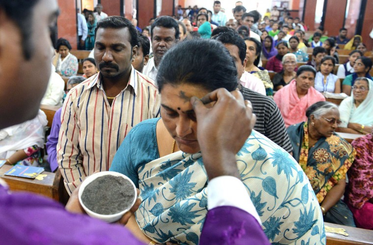An Indian Catholic priest (left) marks the symbol of the cross with ash on the forehead of a Christian devotee during an Ash Wednesday service at Saint Mary's Basilica in Secunderabad, the twin city of Hyderabad, on February 18, 2015. (NOAH SEELAM/AFP/Getty Images)