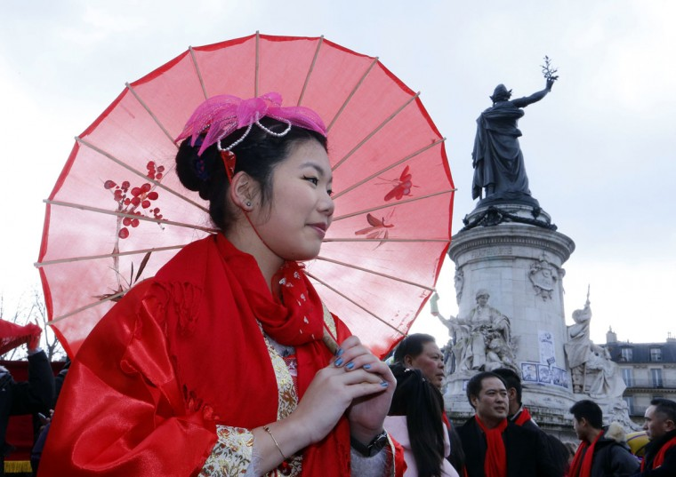 A Chinese woman walks past the statue of Marianne at the Place de la Republique as the Marais district Chinese community celebrates the Chinese Lunar New Year on February 21, 2015, in Paris. (FRANCOIS GUILLOT/AFP/Getty Images)