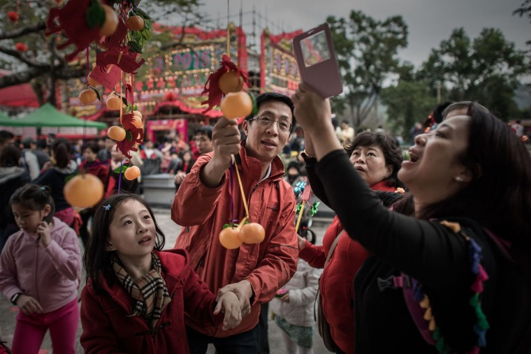 In this picture taken on February 19, 2015, a family take pictures of their wishes tied to plastic oranges hanging from the branches of a special tree in the remote village of Lam Tsuen of Hong Kong's new territories. Carnivals and fireworks are Hong Kong's trademark Chinese Lunar New Year celebrations -- but tens of thousands of people also travel to a remote village to hurl oranges at a tree in hopes of making their wishes come true. (PHILIPPE LOPEZ/AFP/Getty Images)