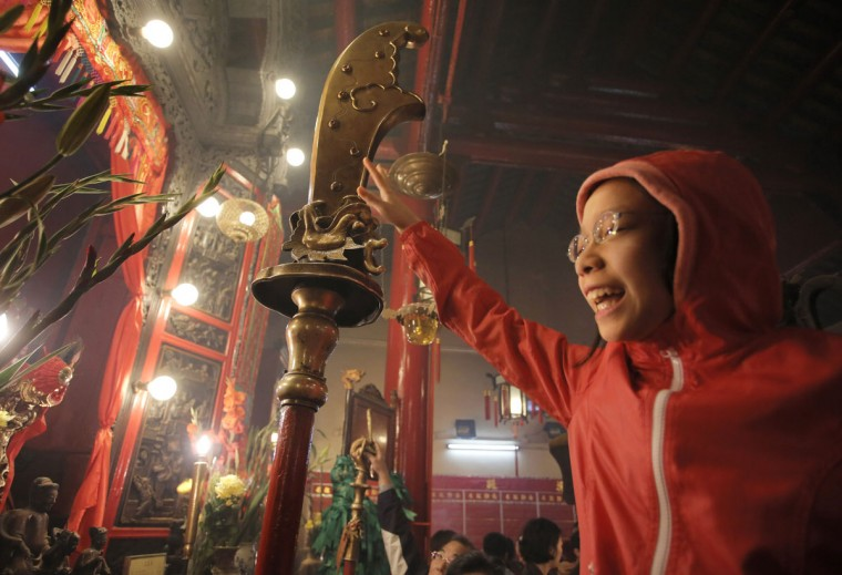 """In this photo taken on Friday, Feb. 20, 2015, Annie Leung, 12, is lifted by her father to touch a guandao - a type of traditional Chinese weapon - in a gesture that is supposed to bring good fortune in the coming year, at Man Mo Temple in central Hong Kong. The temple pays tribute to the God of Literature (""""Man"""" in Chinese) and God of War (""""Mo"""" in Chinese) traditionally worshipped by scholars in ancient China looking to succeed and excel in civil examinations that would win them high positions in the government. (AP Photo/Vincent Yu)"""