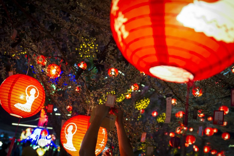 An unidentified woman hangs prayers for luck on a tree at Fo Guang Shan Dong Zen Buddhist Temple decorated with Chinese traditional lanterns in Jenjarom, outside Kuala Lumpur, Malaysia on Saturday, Feb. 21, 2015. (AP Photo/Joshua Paul)