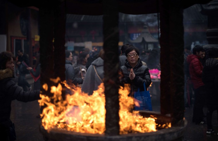 People burn incense as they pray for good fortune at the Jade Buddha Temple on the third day of the Chinese Lunar New Year in Shanghai on February 21, 2015. (JOHANNES EISELE/AFP/Getty Images)